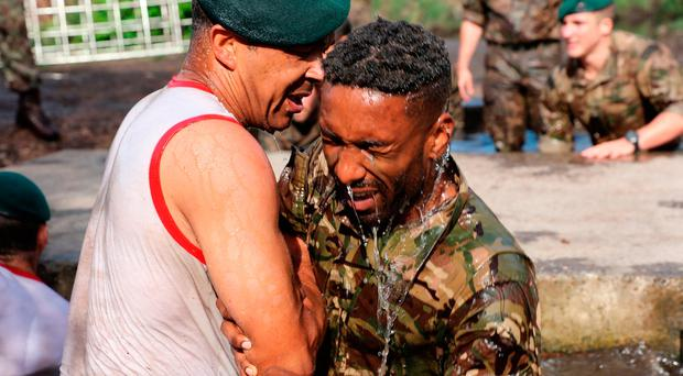 Jermain Defoe exits the 'sheep dip'' on the Royal Marines Endurance Course.