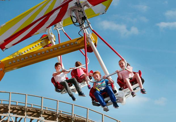Children enjoying a chair-planes ride at the park
