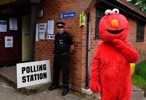 Police and a man dressed as Elmo outside a polling station in the village of Sonning, Berkshire, where Prime Minister Theresa May and her husband Philip are expected to cast their votes later. PA Wire