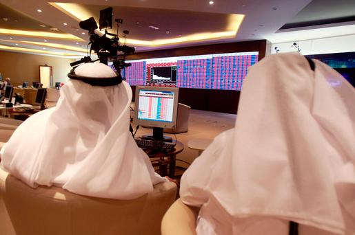 Traders monitor screens displaying stock information at Qatar Stock Exchange in Doha. Photo: Reuters