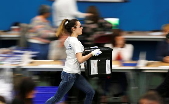 An election worker sprints through the count centre with a ballot box in Sunderland. Picture: Reuters