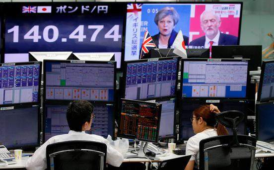 Employees of a foreign exchange trading company work near monitors showing TV news on Britain's general election and the Japanese yen's exchange rate against the British pound in Tokyo