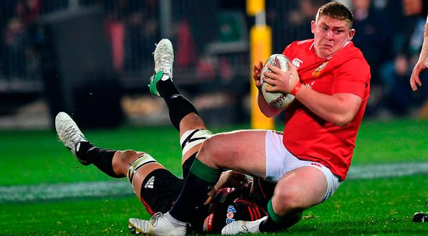 Lions' Tadhg Furlong (R) is tackled by Crusaders' Jordan Taufua