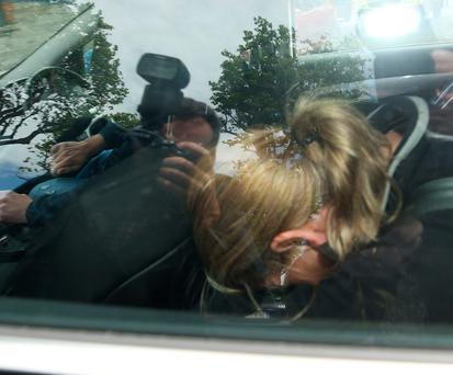 Regina Keogh, who was charged with the murder of Gareth Hutch at the district court leaves in the back of a garda car.