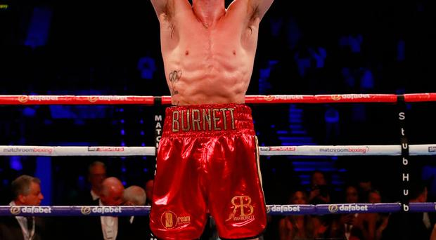 Ryan Burnett celebrates with the belt after winning the fight