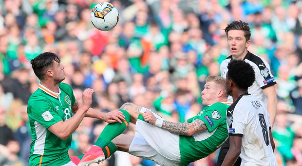 James McClean attempts to acrobatically clear away the danger. Photo: PA