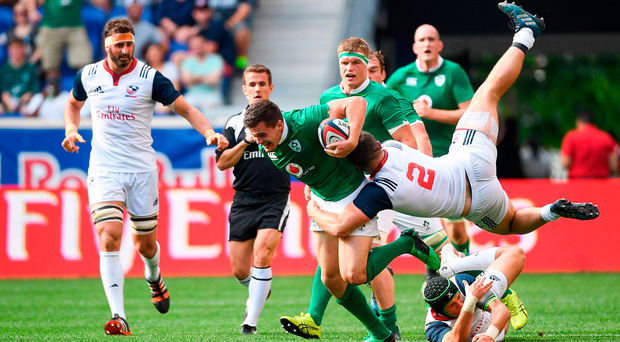 Jacob Stockdale is tackled by Peter Malcolm as he tries to make a break. Photo by Ramsey Cardy/Sportsfile