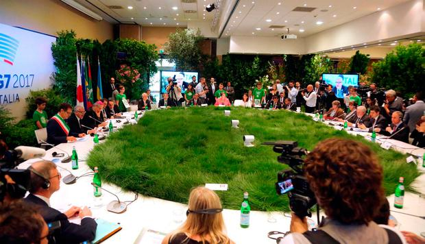Grass covers the round table where environment ministers sit at the opening of a two-day G7 summit on the environment, in Bologna, Italy, Sunday, June 11, 2017. (Giorgio Benvenuti/ANSA via AP)