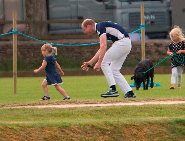 The Duke of Cambridge chases Mia Tindall, daughter of Mike and Zara Tindall, at the Gloucestershire Festival of Polo at Beaufort Polo Club in Tetbury, Gloucestershire