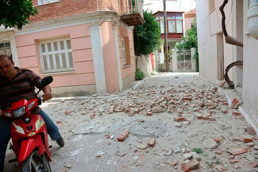 A man with his motorcycle passes next to a damaged house after an earthquake in the village of Plomari on the northeastern Greek island of Lesbos, Monday, June 12, 2017. A Turkish government agency says an earthquake with a preliminary magnitude of 6.2 has shaken western Turkey. The Greek island of Lesbos has also been rattled. (Manolis Lagoutaris/InTime News via AP)