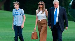 Moving in: Barron and Melania are greeted by Donald Trump at the White House