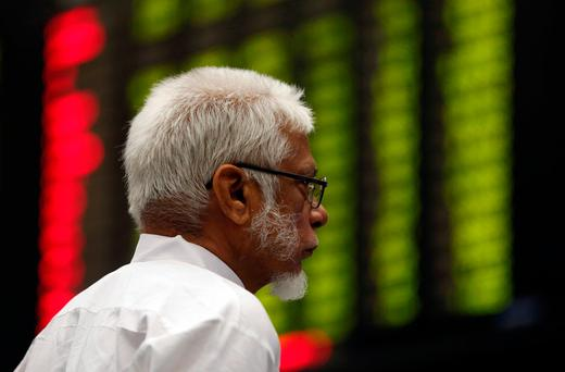 A man monitors an electronic board displaying share market prices during a trading session in the halls of Pakistan Stock Exchange (PSX) in Karachi. Photo: Reuters