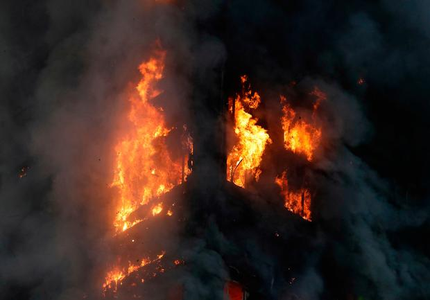 Smoke and flames rise from a building on fire in London, Wednesday, June 14, 2017. Metropolitan Police in London say they're continuing to evacuate people from a massive apartment fire in west London. The fire has been burning for more than three hours and stretches from the second to the 27th floor of the building.(AP Photo/Matt Dunham)