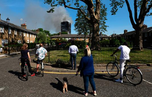 People look at smoke billowing from a tower block severly damaged by a serious fire, in north Kensington, West London, Britain June 14, 2017. REUTERS/Toby Melville