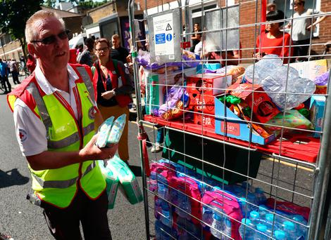 A man hands out refreshments near a tower block severely damaged by a serious fire, in north Kensington, West London, Britain June 14, 2017. REUTERS/Neil Hall