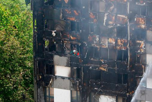 A firefighter photographs damage after a fire engulfed the 24-storey Grenfell Tower