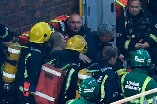 The man, believed to be a blind pensioner, is rescued by fire fighters after a huge fire engulfed the 24 storey residential Grenfell Tower block