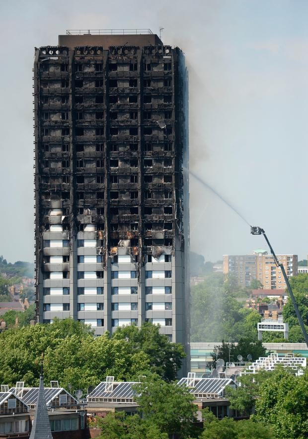 Firefighters spray water after a fire engulfed the 24-storey Grenfell Tower in west London. Photo: Victoria Jones/PA Wire