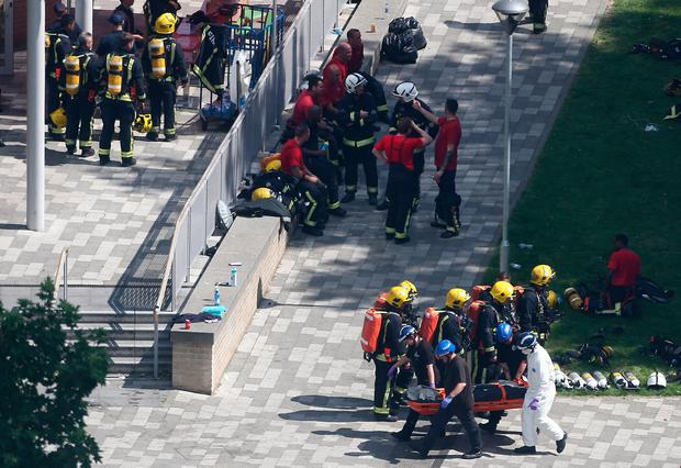 Emergency services personnel carry a body bag on a stretcher away from the scene. Photo: REUTERS
