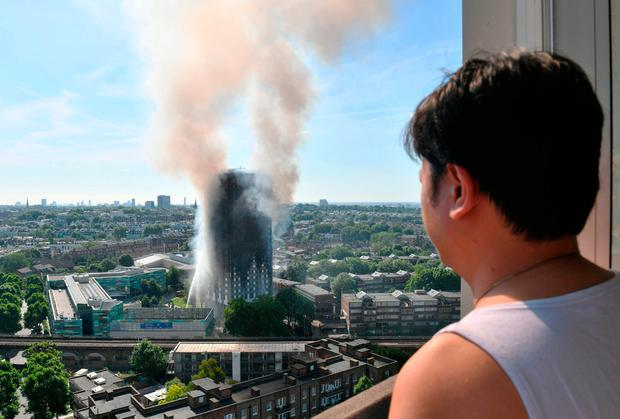 A resident looks on as smoke billows from Grenfell Tower. Photo: PA