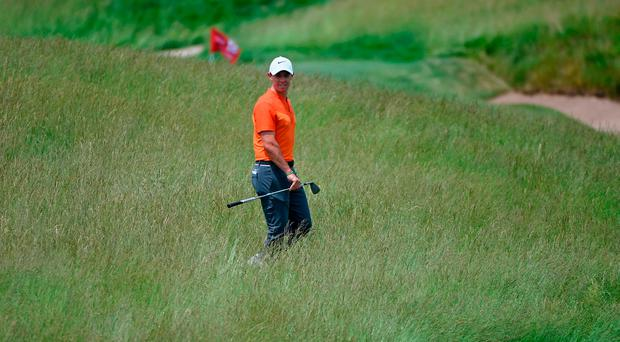 Rory McIlroy traipses through the heavy rough at Erin Hill yesterday. Photo: Getty