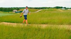 Jim Mackay, caddy for Phil Mickelson, walks the course alone yesterday. Photo: Getty