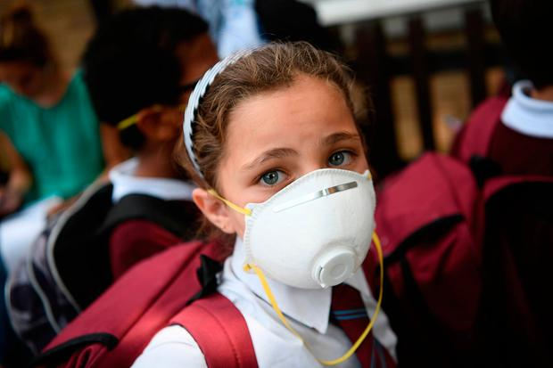 A young girl wears a protective face mask near the burning 24 storey residential Grenfell Tower block in Latimer Road, West London. Photo: GETTY