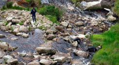 Gardaí search the the Glenmacnass Waterfall in the Wicklow Mountains where some of Ms O'Connor's remains were found. Photo: Collins