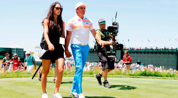 Rickie Fowler walks off the ninth green with Allison Stokke after shooting a seven-under-par 65 in the first round of the US Open at Erin Hills. Photo by Jamie Squire/Getty Images