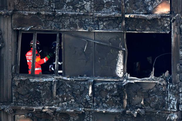 Emergency workers and police inspect inside the remains of Grenfell Tower yesterday Photo: Chris J Ratcliffe/Getty Images