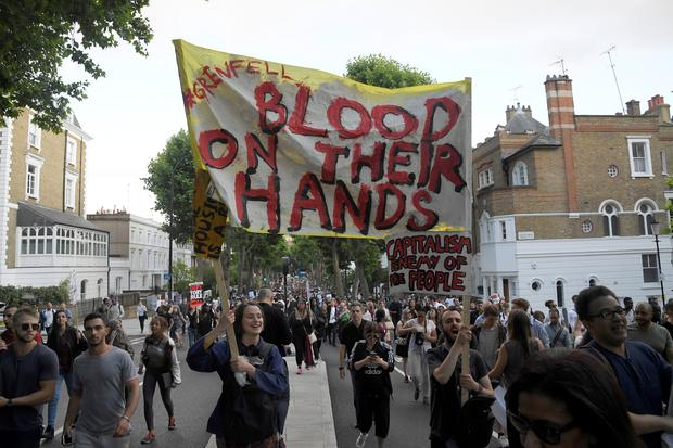 Demonstrators hold up banners during a march in Kensington, following the fire that destroyed The Grenfell Tower block, in north Kensington, West London, Britain June 16, 2017. REUTERS/Toby Melville
