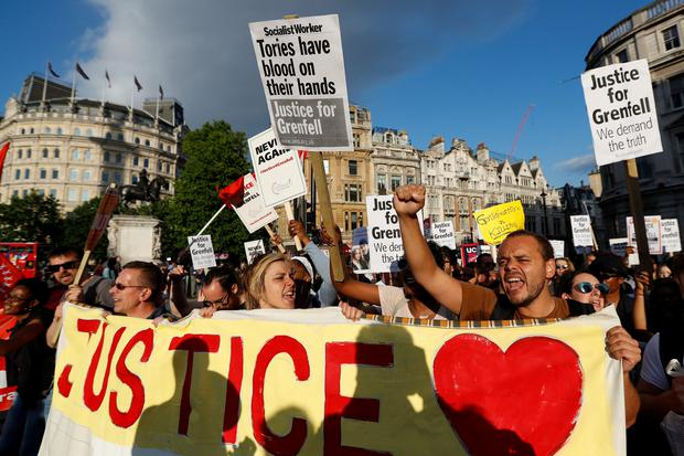 Demonstrators hold up banners during a march in Westminster, following the fire that destroyed The Grenfell Tower block, in north Kensington, West London, Britain June 16, 2017. REUTERS/Peter Nicholls