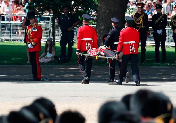 A Guardsman is carried off after fainting during the Trooping the Colour ceremony at Horse Guards Parade, central London, as the Queen celebrates her official birthday.