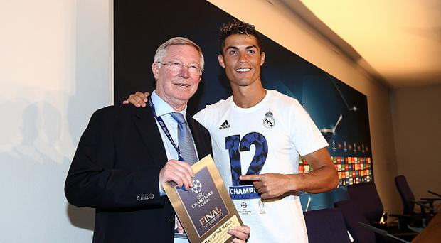 In this handout image provided by UEFA, Cristiano Ronaldo of Real Madrid poses with the Man of the Match award and Sir Alex Ferguson after the UEFA Champions League Final between Juventus and Real Madrid at National Stadium of Wales on June 3, 2017 in Cardiff, Wales. (Photo by Handout/UEFA via Getty Images)