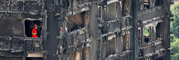 GRIM TASK: Members of the emergency services work on the middle floors of the charred remains of the Grenfell Tower block in Kensington, west London, following the devastating fire. Photo: Tolga Akmen/Getty