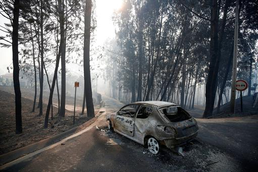 A burned car is seen in the aftermath of a forest fire near Pedrogao Grande, in central Portugal