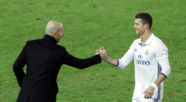 Cristiano Ronaldo (R) of Real Madrid shakes hands with head coach Zinedine Zidane (L) as he is substituted during the FIFA Club World Cup final match between Real Madrid and Kashima Antlers at International Stadium Yokohama on December 18, 2016 in Yokohama, Kanagawa, Japan. (Photo by The Asahi Shimbun via Getty Images)