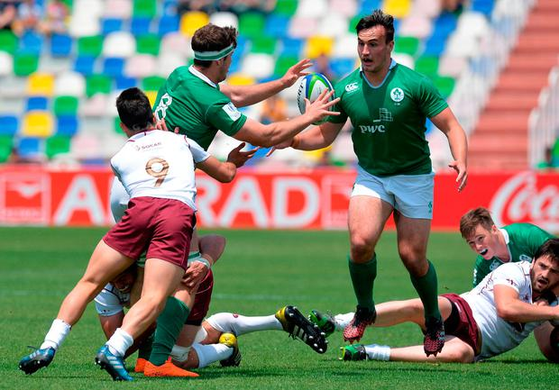 Caeian Doris of Ireland offloads the ball to team mate Ronan Kelleher. Photo by Mark Runnacles/Getty Images