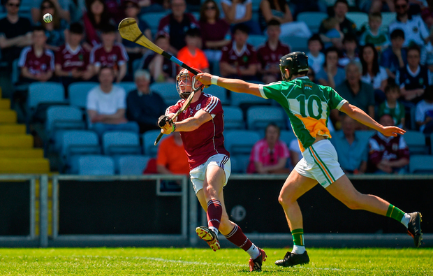 Conor Whelan of Galway scores a point while under pressure from Pádraic Guinan of Offaly Photo: Seb Daly/Sportsfile
