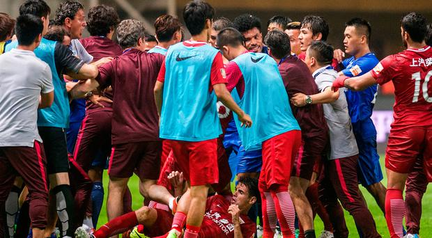 Shanghai SIPG players, red jerseys, and Guangzhou R&F players, blue jerseys, tussle after Shanghai's Oscar was tackled on the ground, during their Chinese Super League match in Guangzhou in south China's Guangdong province