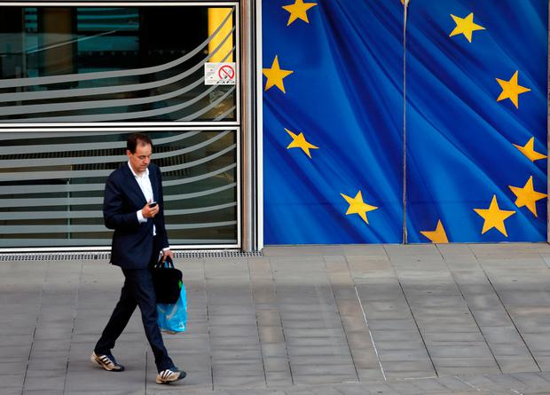 A man checks his phone outside the EU headquarters as Britain and the EU launch Brexit talks in Brussels, June 19, 2017. REUTERS/Francois Lenoir