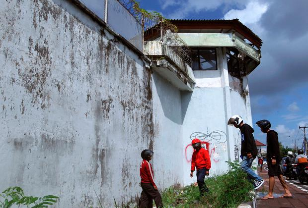 Residents observe a hole on the ground through which four foreign inmates have escaped from Kerobokan prison in Bali, Indonesia, Monday, June 19, 2017. (AP Photo/Firdia Lisnawati)