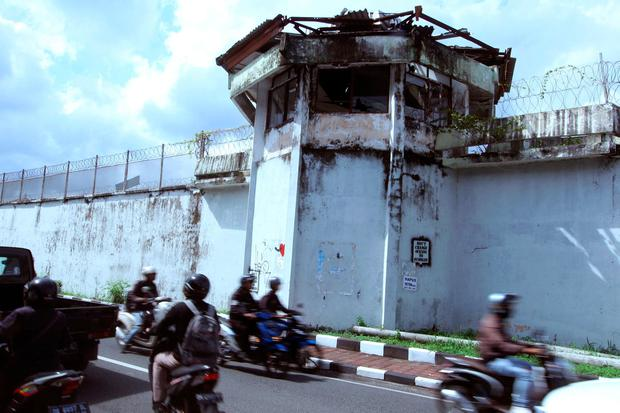 Bikers drive by a wall of Kerobokan prison from which four foreign inmates have escaped in Bali, Indonesia, Monday, June 19, 2017. (AP Photo/Firdia Lisnawati)