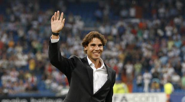 Tennis player Rafael Nadal greets prior to the start of the UEFA Champions League group G match between Real Madrid and AFC Ajax at Estadio Santiago Bernabeu on September 15, 2010 in Madrid, Spain. (Photo by Angel Martinez/Getty Images)