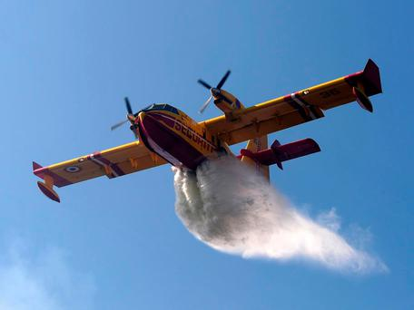 A Canadair amphibious aircraft drops its load over a wildfire in central Portugal in 2013 Getty