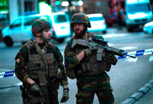 Soldiers speak as they stand alert in a cordoned off area on a street outside Gare Centrale in Brussels. AFP/Getty Images