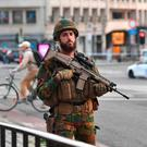 A Belgian Army soldier stands outside Central Station after a reported explosion in Brussels on Tuesday