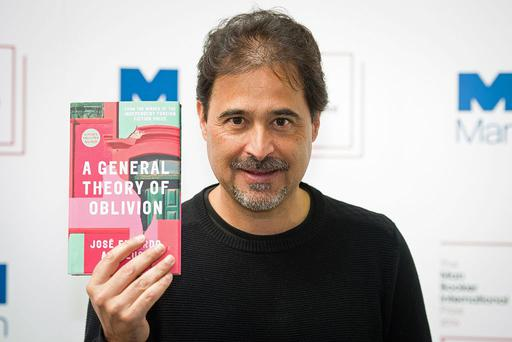Angolan author Jose Eduardo Agualusa poses for a photograph with his book A General Theory of Oblivion at a photocall in London on May 15, 2016, ahead of the announcement of the winner of the 2016 Man Booker International Prize. PHOTO: LEON NEAL/AFP/Getty Images