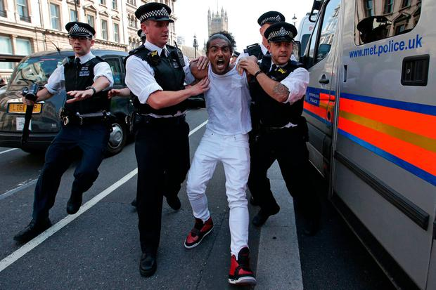A man is arrested by police as protesters gather in Parliament Square after marching through central London yesterday. Photo: Getty