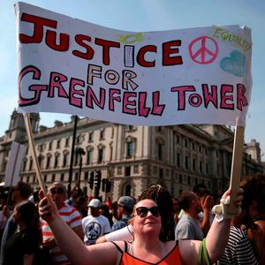 A protester holds up a sign asking for 'Justice for Grenfell' following the deadly fire at Grenfell Tower. Photo: Getty